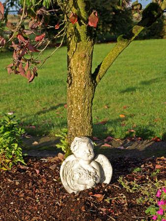 bark mulch: Angel garden statue sitting next to a tree