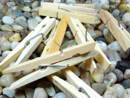 household objects equipment: wooden pegs on river stone  background Stock Photo