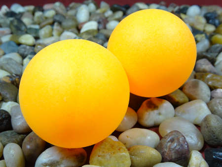 river rock: 2 yellow table tennis balls in river rock background