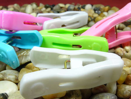 household objects equipment: colourful plastic  pegs on river stone  background Stock Photo