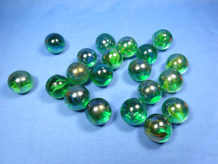 marbles close up: green marbles in blue background close up