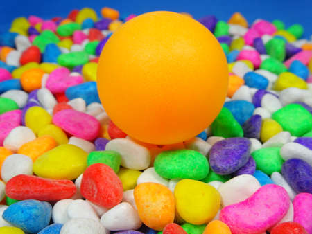 river rock: A  table tennis ball in colourful river rock background Stock Photo