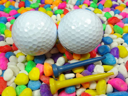Two golf ball and tees on colourful river stone background photo