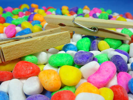 household objects equipment: wooden pegs on colourful stone  background