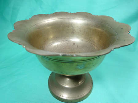 bronze bowl: Malaysian antique hand washer bowl on light green background