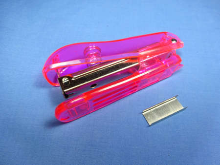 staplers: A pink stapler in blue background