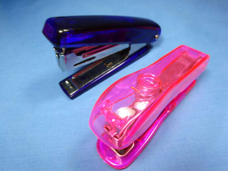staplers: Pink  and blue staplers in blue background