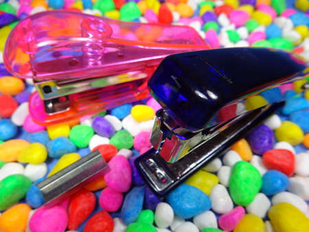 staplers: Pink  and blue staplers in colourful stone background Stock Photo