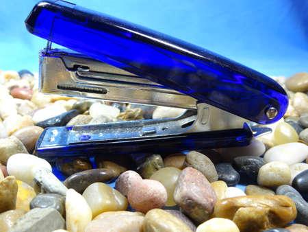 grapadora: Una grapadora azul en el fondo de piedra de r�o