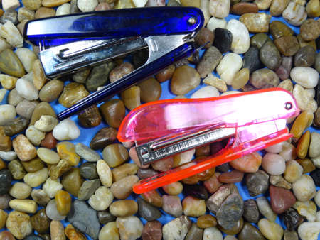 staplers: Blue and pink staplers in  river stone background