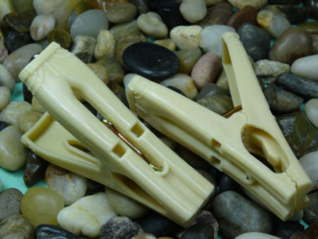 household objects equipment: white plastic  pegs on river stone  background Stock Photo