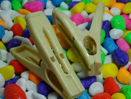 white plastic  pegs on colourful stone  background photo