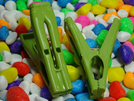 household objects equipment: green plastic  pegs on colourful  stone  background