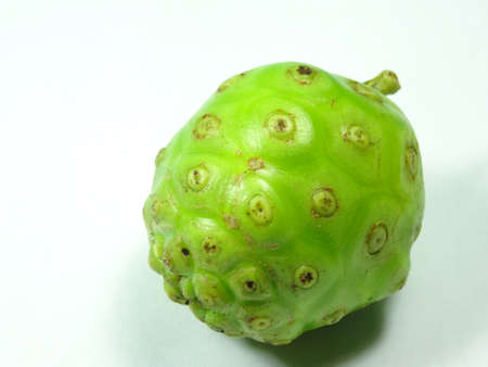 great morinda: unripe  cheese fruit close up on white background