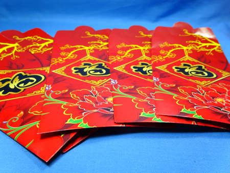 packets: chinese new year green packets close up in blue background.