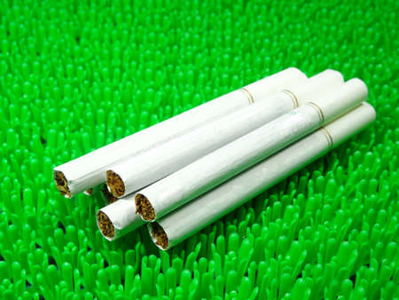menthol: white menthol cigarette on artificial green grass background Stock Photo