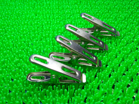 household objects equipment: steel pegs on artificial green grass  background