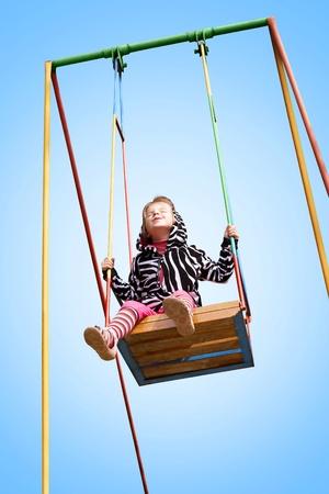 happy little girl swinging on a swing on a blue background Standard-Bild