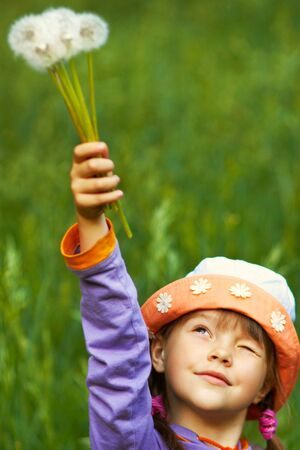 girl in a hat with dandelions in his raised hand against the background of green grass