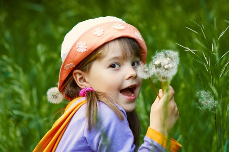 funny girl with a bouquet of dandelions on background of green grass photo
