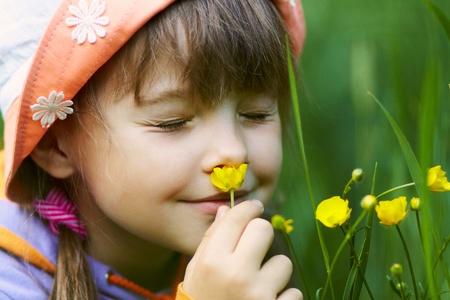 녹색 배경에 노란색 꽃 냄새 나사 - 업 소녀의 근접 촬영 스톡 콘텐츠