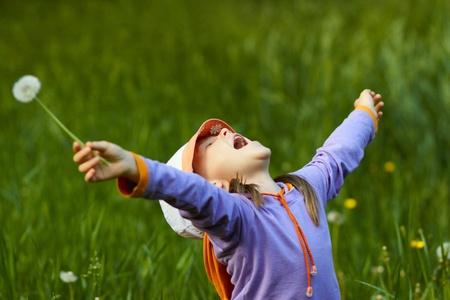 민들레 팔을 아주 행복 소녀 녹색 잔디의 배경에 뻗은