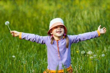 행복 한 소녀 민들레 무기 녹색 잔디의 배경에 대해 뻗은