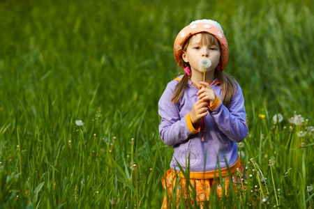 girl in a field of green grass holding dandelion and looks into the camera