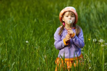 meisje in een veld van groen gras houden paardebloem en kijkt in de camera