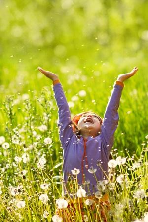 gelukkig meisje met handen omhoog in het veld met pluizige paardebloemen