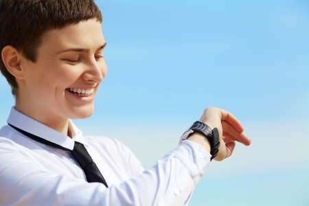 stylish young businesswoman looks at his watch on background sky photo