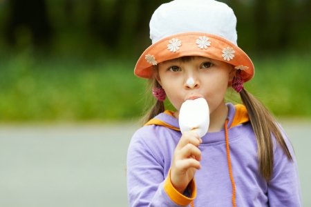 girl eating ice cream in a hat and looks into the camera