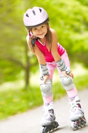 Klein meisje in het rolschaatsen op een park