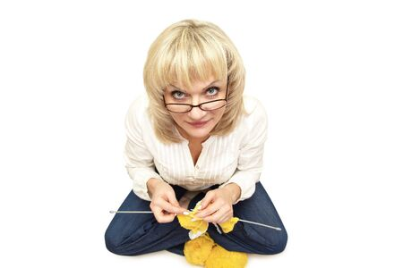 adult woman in glasses is sitting cross-legged and knitting on a white background  isolated Stock Photo