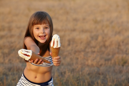 eats: happy little girl holds out of ice cream Stock Photo