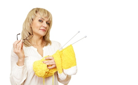 adult woman holding yarn and glasses and looking at the camera on a white background  isolated
