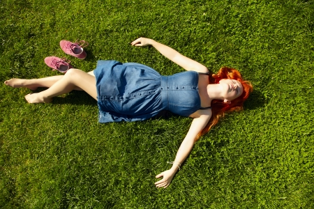 草の上、休憩が横になっている美しい赤毛の若い女の子