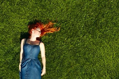 아름 다운 빨간 머리 소녀 거짓말 잔디에 휴식