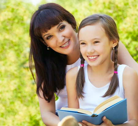 mother with her daughter reading a book in the park photo