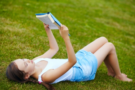 girl lying on the grass in the park and reading a book photo