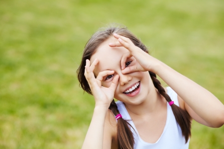 portrait of a cheerful girl who portrays glasses hands, over green background photo