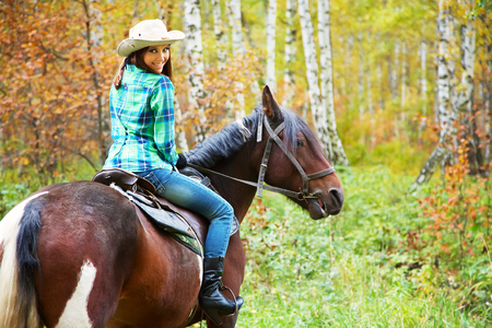 Attractive smiling woman in a hat riding a horse photo