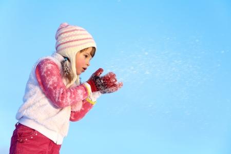 portret van een meisje rond te lopen buiten in de winter, het blazen op sneeuw
