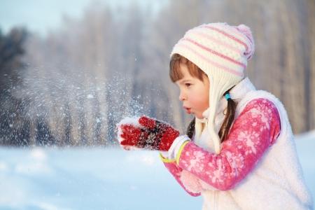 portret van een meisje rond te lopen buiten in de winter, spelen met sneeuw