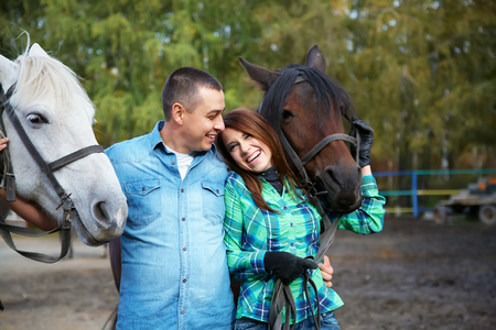 loving couple on a walk with horses