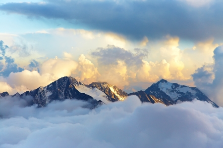alpine landscape with peaks covered by snow and clouds