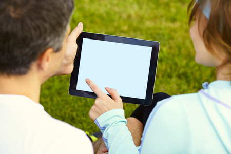 sports couple sitting on the grass using a digital tablet after training Standard-Bild