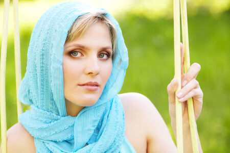 outdoor closeup portrait of a beautiful middle aged blonde woman in blue headscarf photo