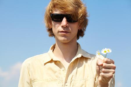 giver: Retrato de un hombre joven con gafas de sol de la flor que da