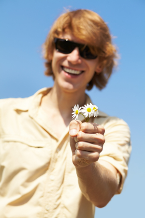 giver: Retrato de un hombre joven con gafas de sol de la flor que da. foco en las flores
